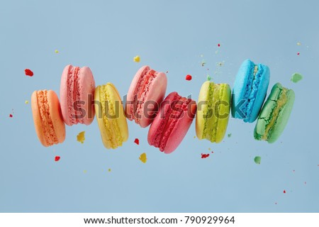 Different types of macaroons in motion falling on blue background. Sweet and colourful french macaroons falling or flying in motion.