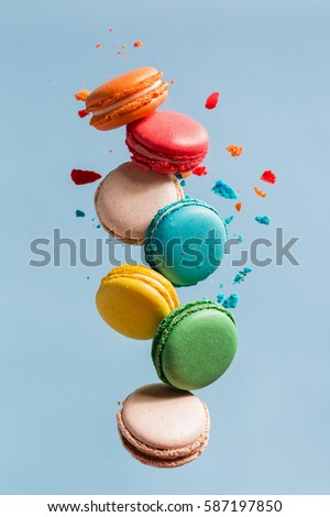 Different types of macaroons in motion falling on light  blue background. Sweet and colorful french macaroons falling or flying in motion.  #587197850