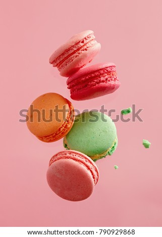 Different types of macaroons in motion falling on pink background. Sweet and colourful french macaroons falling or flying in motion.  #790929868