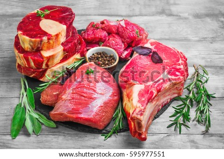 Different types of meat beef on round board. Herbs for an assortment of beef meat basil, thyme, rosemary, sage leaves, pepper. Light white wooden background.    Top view from above and copy space.