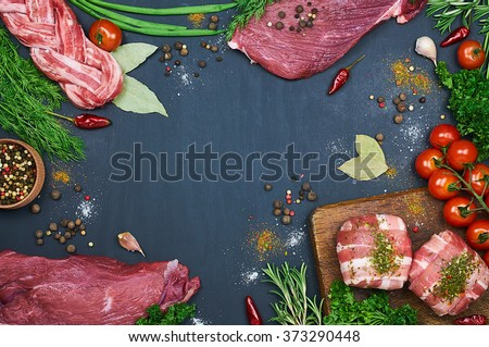 Different types of meat. Fresh butcher cut meat assortment on dark background. Decorated with vegetables and spice. Top view. Close-up