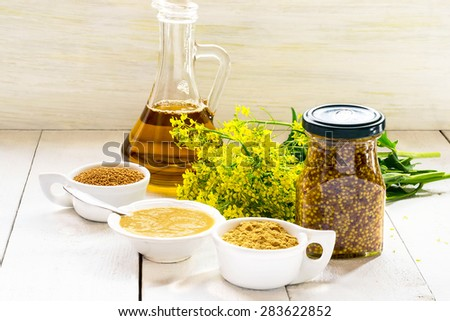 Different types of mustard: powder, seeds, cooked Dijon mustard, spicy Russian mustard, mustard oil, mustard flowers on a white wooden table. Selective focus #283622852