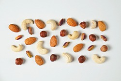Different types of nuts scattered on isolated white background. Nutrient dense vegan snacks. Clean eating concept. Close up, copy space for text, top view, flat lay.