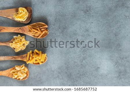 Different types of pasta lying in wooden spoons lying on grey table. Penne, tortellini, fuzilli, and farfalle. Copy space. Horizontal.