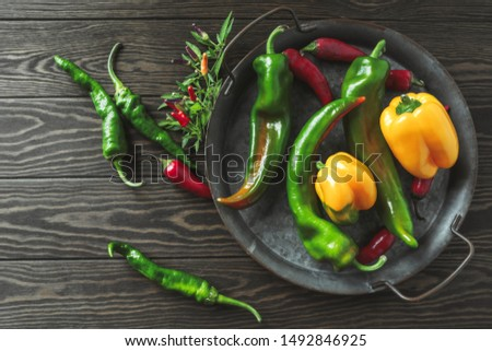 different types of peppers on an iron tray: sweet yellow pepper, chili pepper, green pepper #1492846925