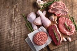 Different types of raw meat - beef, pork, lamb, chicken on a wooden board with copy space