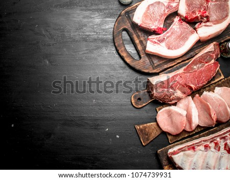 Different types of raw pork meat and beef. On the black chalkboard.