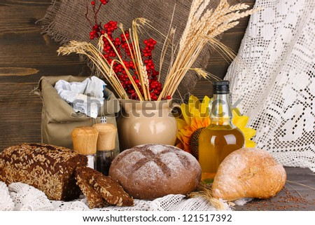 Different types of rye bread on wooden table on autumn composition background