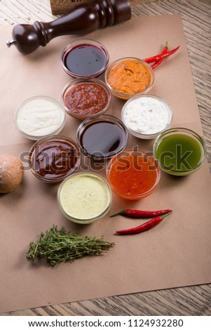 Different types of sauces background. Set of sauces - ketchup, mayonnaise, mustard, soy sauce, bbq sauce, pesto, mustard grains and pomegranate sauce #1124932280