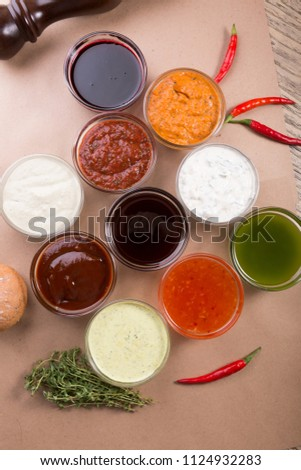 Different types of sauces background. Set of sauces - ketchup, mayonnaise, mustard, soy sauce, bbq sauce, pesto, mustard grains and pomegranate sauce #1124932283
