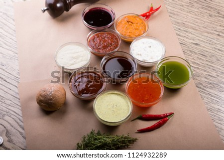 Different types of sauces background. Set of sauces - ketchup, mayonnaise, mustard, soy sauce, bbq sauce, pesto, mustard grains and pomegranate sauce #1124932289