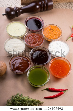 Different types of sauces background. Set of sauces - ketchup, mayonnaise, mustard, soy sauce, bbq sauce, pesto, mustard grains and pomegranate sauce #1126102493