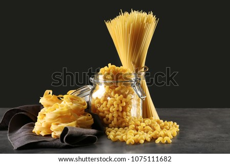 Different uncooked pasta on table against dark background