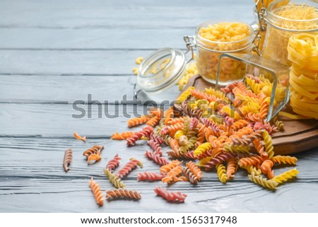 Different uncooked pasta on wooden table