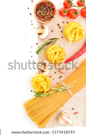 Different uncooked pasta with spices and vegetables on white background