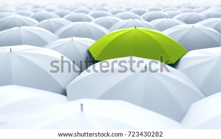 Different, unique and standing out of the crowd green umbrella