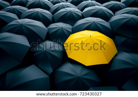 Different, unique and standing out of the crowd yellow umbrella
