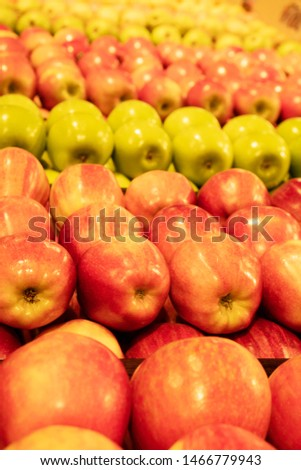 Different varieties of apples in a grocery store, vertical composition.