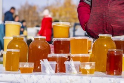 Different varieties of Bashkir bee honey poured into containers of different sizes for sale.