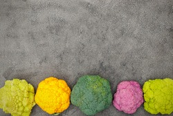 Different varieties of cabbage and cauliflower on gray background