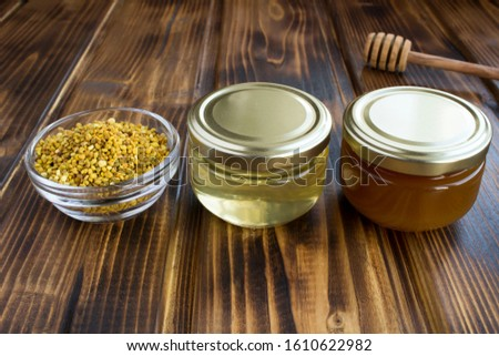 Different varieties of honey in small glass jars and bee pollen on the  brown wooden background. Closeup.