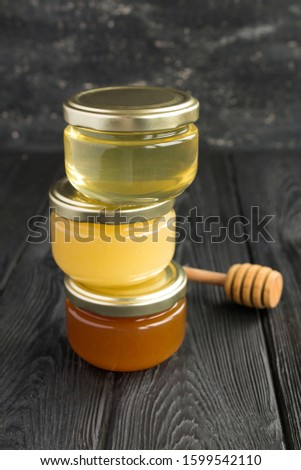Different varieties of honey in small glass jars on the black  background. Location vertical. Closeup.