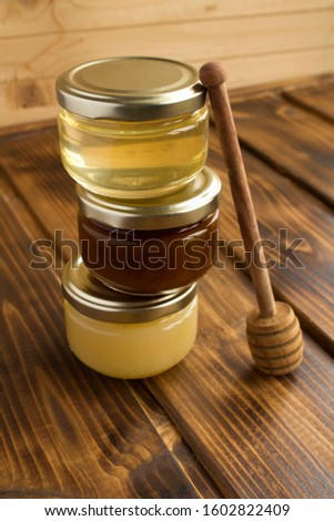 Different varieties of honey in small glass jars on the  brown wooden background. Location vertical. Closeup.