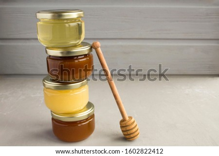 Different varieties of honey in small glass jars on the grey  background.  Closeup.