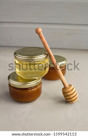 Different varieties of honey in small glass jars on the grey  background. Location vertical. Closeup.