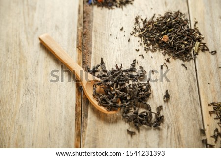 different varieties of natural tea on a bamboo spoon on a wooden background