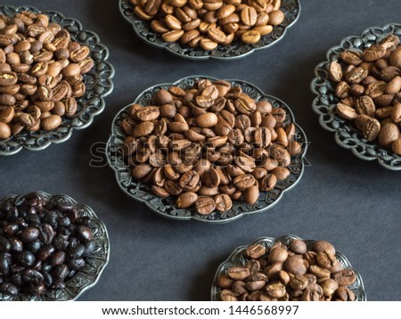 Different varieties of roasted coffee beans on a black background.