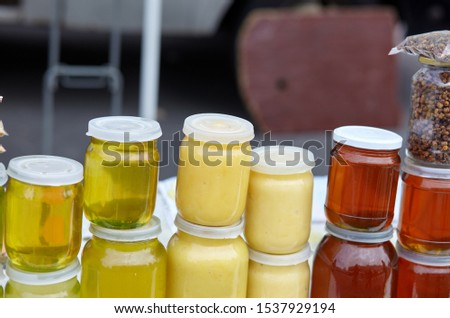 Different varieties of sweet golden and white honey at the farmers market. Natural honey in various jars.Vitamin healthy food