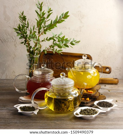 Different varieties of tea in teapots and delicious pastries