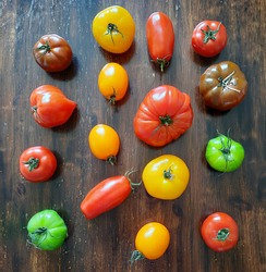 Different varieties of tomato on a wooden kitchen table