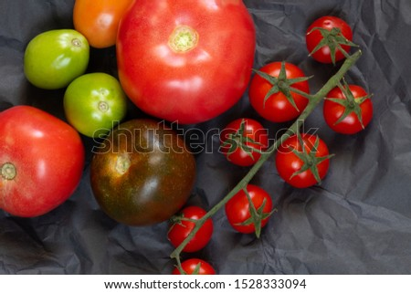 different varieties of tomatoes lie on a black background photo studio