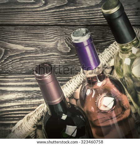 different varieties of wine bottles in a basket on the table. toned image. focus on the bottle neck #323460758