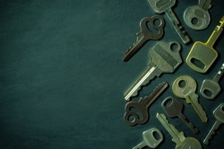 Different variety of vintage keys are placed on black wooden floor in darkness background. Closeup and copy space on left. Idea for keys to solving business problems. Concept for security or privacy.