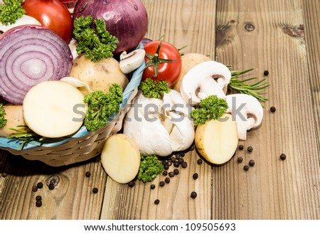 Different Vegetables in a basket on wooden background