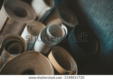 Different wallpaper rolls. Various textures and colours.