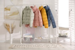 Different warm jackets on rack in stylish room interior