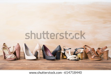 Different woman's shoes on wooden floor #614718440