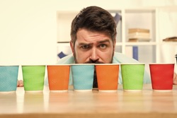 Difficult choice. decision-making. serious and sad man with colorful coffee cups. Many cups of coffee. hard choice to make. i need more coffee. low energy. Taking decisions. mature hipster man.