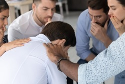 Difficult moment. Compassionate multiethnic colleagues friends supporting depressed frustrated young man in hard period of life, diverse partners showing empathy to male mate on group therapy session