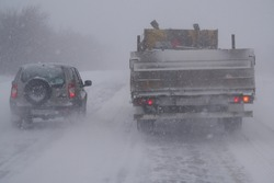 Difficult road situation, snowstorm, snowfall. Overtaking a truck in poor visibility. Part of the image is blurred.