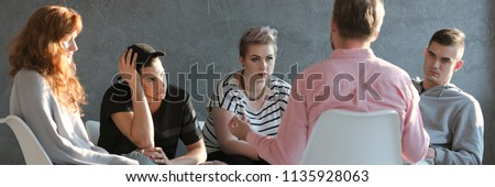 Difficult teenagers listening to psychotherapist during meeting of support group #1135928063