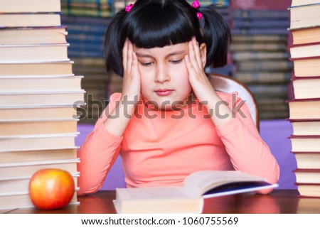 Difficulties in school learning concept. Cramming child girl among books. Preparing to school exam test.