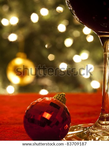Diffused lights and ornaments from a Christmas tree form the background for a close-up of a glass of red wine and a red ornament.