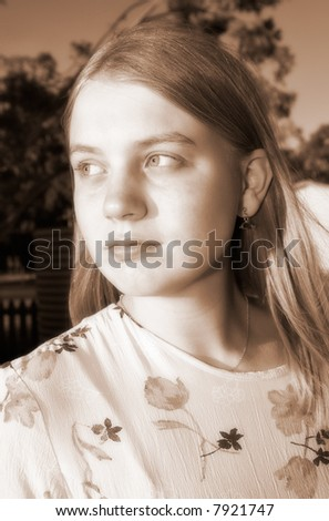 diffused sepia image of teenage girl or young woman looks off wistfully