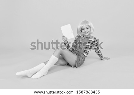 Dig into reading. Cute little girl read book yellow background. Adorable small child enjoy reading. Library and reading hall. Reading feeds imagination.