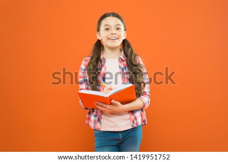 Dig into reading. Cute small child reading a book on orange background. Adorable little girl learn reading and writing. Home reading and schooling.